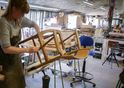 Praktikant Cæcilie Andrea Bue afpudser en stol
